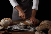 Fotografie partial view of male baker in apron cutting bread on sackcloth by knife on wooden table