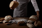 partial view of male baker in apron holding bread over table with knife, bread and sackcloth