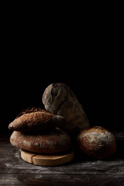 close up shot of various types of bread and cutting board on wooden table covering by flour isolated on black background