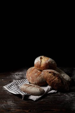 closeup view of various types of bread and sackcloth on wooden table covering by flour isolated on black background