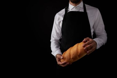 cropped shot of male baker in apron holding bread isolated on black background