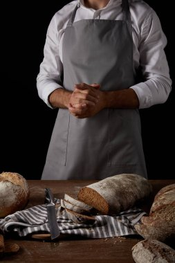 cropped shot of male baker in apron standing near table with knife, sackcloth and bread