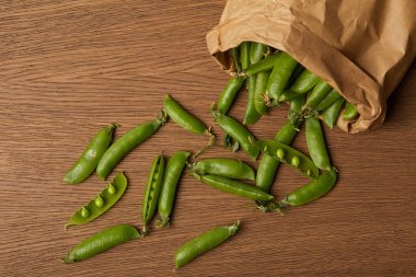 top view of pea pods spilled from paper bag on wooden table