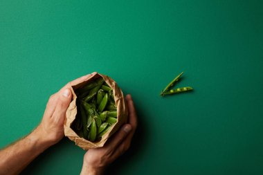 cropped shot of man holding paper bag with pea pods on green surface