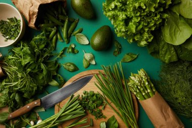 top view of various ripe vegetables with wooden cutting board and knife on green surface