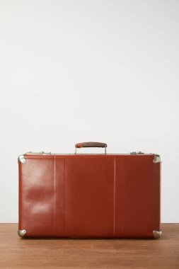 Closed leather suitcase on wooden background