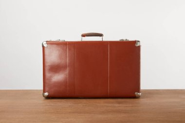 Vintage brown leather suitcase on wooden table