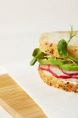 close-up shot of sandwich with radish slices and pea shoots on wooden cutting board