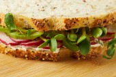 close-up shot of vegetarian sandwich with radish slices and pea shoots on wooden surface
