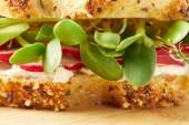 Detailní záběr zdravý sendvič s plátky ředkviček a hrachové výhonky na dřevěném prkénku