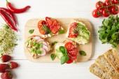 felülnézete vegetáriánus szendvicsek körül fehér fa felületre alapanyagokból vágódeszka