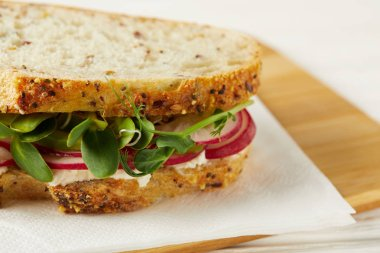 close-up shot of fresh sandwich with radish slices and pea shoots on wooden cutting board