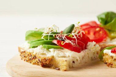 close-up shot of delicious sandwich with avocado, tomato and pea shoots