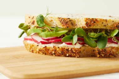 close-up shot of tasty sandwich with radish slices and pea shoots on wooden cutting board