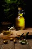 olivový olej v láhve a mísy na dřevěných desek