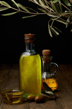 Bottles of various olive oil on wooden surface stock vector