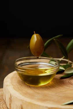 aromatic olive oil dripping from olive fruit above bowl on wooden board