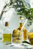 Fotografie glass with spoon and green olives, jar, various bottles of aromatic olive oil with and branches on white table