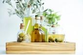 Fotografia vetro con il cucchiaio ed olive verdi, jar, varie bottiglie di olio doliva aromatizzato e rami sul cassetto di legno