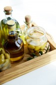 Fotografie jar and glass with green olives, various bottles of aromatic olive oil with and branch on wooden tray