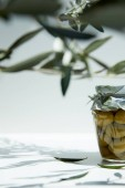 Fotografie jar of aromatic oil with green olives and branches on white table