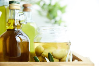 close up shot of jar with green olives, bottles of aromatic olive oil with and branches on wooden tray