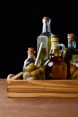 different bottles of aromatic olive oil and jar with green olives on wooden table on black background