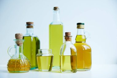 different bottles of aromatic olive oil and jar on white background