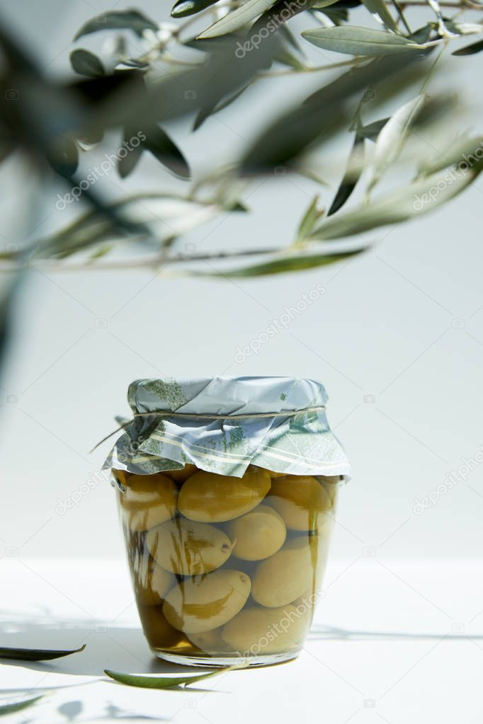jar of aromatic oil with green olives and branches on white table
