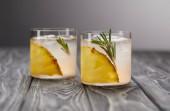 két pohár limonádé az ananász darabokat, a jeget és a rozmaring a szürke fából készült asztali