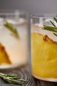 Fotografie Aufnahme von zwei Gläsern Limonade mit Ananasstücken, Eiswürfel und Rosmarin auf grauen hölzernen Tischplatte hautnah