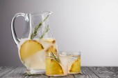 edény és két pohár limonádé az ananász darabokat, a jeget és a rozmaring a szürke fából készült asztali