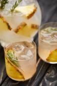 Fotografie částečný pohled džbán a dvě sklenice limonády s ananasem kousky, kostky ledu a rozmarýnem na šedý dřevěný stůl