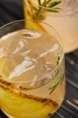 Fotografie selektiven Fokus von zwei Gläsern Limonade mit Ananasstücken, Eiswürfel und Rosmarin auf grauen hölzernen Tischplatte