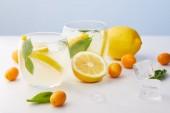 két pohár limonádé, mentalevél, jégkockák és citromos szelet körül kumquats és a citrom, a kék háttér