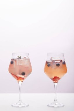 two glasses of lemonade with ice cubes, rosemary, strawberries and blueberries isolated on grey background