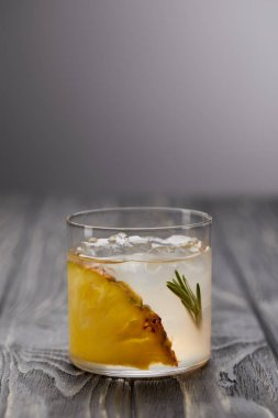 glass of lemonade with rosemary, ice cubes and pineapple on grey wooden table