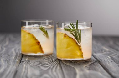 two glasses of lemonade with pineapple pieces, ice cubes and rosemary on grey wooden tabletop