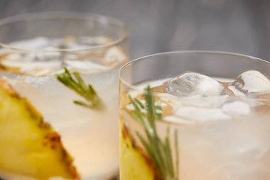 selective focus of two glasses of lemonade with pineapple pieces, ice cubes and rosemary on grey wooden tabletop