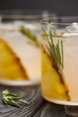 close up image of two glasses of lemonade with pineapple pieces, ice cubes and rosemary on grey wooden tabletop