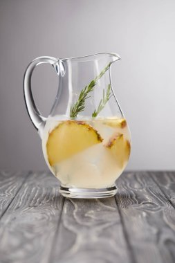 jug of lemonade with rosemary and pineapple pieces on grey wooden tabletop