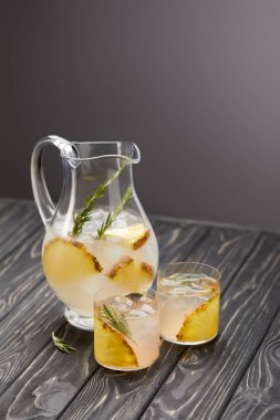 jug and two glasses of lemonade with pineapple pieces, ice cubes and rosemary on grey wooden tabletop