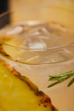 selective focus of glass of lemonade with ice cubes, pineapple pieces and rosemary