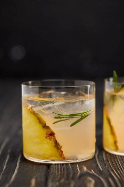 partial view of two glasses of lemonade with pineapple pieces, ice cubes and rosemary on grey wooden tabletop