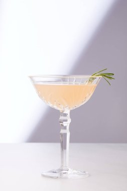 alcohol cocktail in glass with rosemary on white tabletop