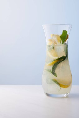 jug of lemonade with mint leaves, ice cubes and lemon slices on blue background