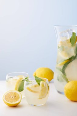 jug and two glasses of lemonade with mint leaves, ice cubes and lemon slices on blue background
