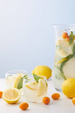 jug and two glasses of lemonade with mint leaves, ice cubes and lemon slices surrounded by kumquats and lemons on blue background