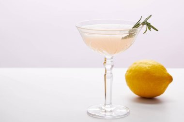 glass of cocktail with rosemary and lemon on purple background