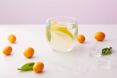 glass of lemonade with mint leaves and lemon slices surrounded by ice cubes, kumquats on purple background